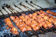 Appetizing pieces of pork meat are strung on skewers and have been frying on a grill.  stock photo