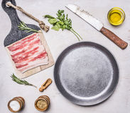 Appetizing pieces of raw bacon in a frying pan with oil, stabbed, herbs, salt and spices wooden rustic background top view clos Royalty Free Stock Photo