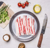 Appetizing pieces of raw bacon in a frying pan with oil, stabbed, herbs, salt and spices wooden rustic background top view clos Stock Photo