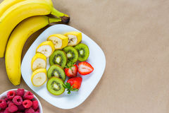 Appetizing plate of fresh fruits. Appetizing plate of fresh bananas, strawberries and kiwis beautifully laid out, and a small bowl of raspberries standing nearby Stock Photos