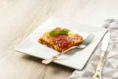 Appetizing portion of lasagna on a white plate with tomato sauce. An appetizing portion of lasagna on a white plate topped with tomato sauce Stock Photography
