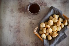 Air profiteroles on a napkin in the basket. A Cup of hot coffee on a beautiful background. stock photos