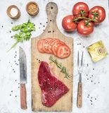 Appetizing raw beef steak with tomatoes, knife and fork for meat on a vintage chopping board, around laid out ingredients, seasoni. Appetizing raw beef steak stock images