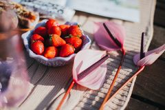 Appetizing red strawberry is in a bowl on the table. Appetizing strawberries and a beautiful pink Anthurium decorate the picnic table stock image