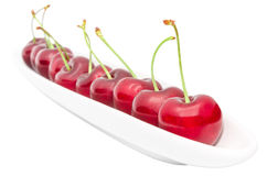 Appetizing ripe cherry berry row on long olive dish. Isolated on white Stock Photography