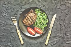 Appetizing roasted meat. Grilled well-done beef steak with with herbs and spices on cutting board and cutlery, flat lay. Restauran royalty free stock photos