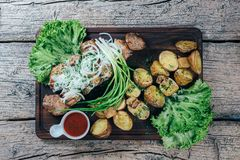 Appetizing roasted pork pieces on the grill, presented on a wooden board, along with leaves of green salad and potatoes with tomat. O sauce stock photos