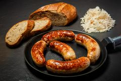 Appetizing ruddy meat wieners fried in large frying pan. Appetizing ruddy meat wieners fried in large pan served with sliced rye bread and sauerkraut on black royalty free stock image
