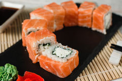 Appetizing salmon rolls. Japanese sushi, closeup. Appetizing and fresh set of rolls with salmon, philadelphia cheese served on black slate on restaurant table Royalty Free Stock Photography