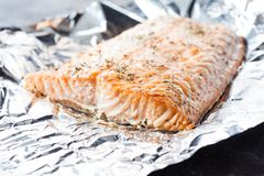 Baked salmon on the foil. Appetizing salmon steak baked with herbs in aluminum foil Stock Images