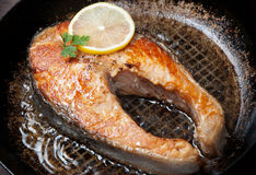 Appetizing salmon steak on a frying pan Stock Image