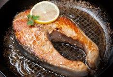 Appetizing salmon steak on a frying pan Stock Image