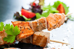 Appetizing salmon and tuna skewer. Macro close up of appetizing char broiled salmon and tuna skewer seasoned with herbs royalty free stock image