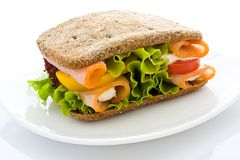 Appetizing sandwich. From rye bread with a ham and salad on a white plate close up Stock Photos