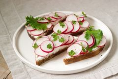 Appetizing sandwiches of rye bread with curd cheese, radishes and lettuce. Rustic style. Appetizing sandwiches of rye bread with curd cheese, radishes and Royalty Free Stock Photo