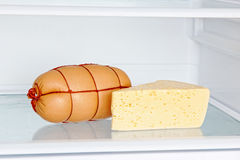 Appetizing sausage and cheese on refrigerator shelf Royalty Free Stock Image