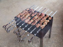 Appetizing shish kebab of lamb with fried onions on the grill Stock Photography