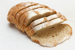 Appetizing sliced bread taken closeup on white fabric. Stock Image