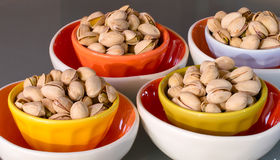 Appetizing snack calorie pistachio nut in colorful bowls Stock Image