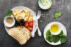 Appetizing snack with fried cheese haloumi, olives, bruschetta, tomatoes, olives, pine nuts, olive oil, honey and. Appetizing snack with fried cheese haloumi Royalty Free Stock Image