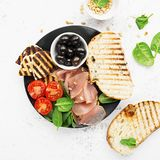 Appetizing snack with fried cheese haloumi, olives, bruschetta, tomatoes, olives, pine nuts, olive oil, honey and. Appetizing snack with fried cheese haloumi Stock Images
