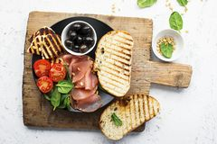 Appetizing snack with fried cheese haloumi, olives, bruschetta, tomatoes, olives, pine nuts, olive oil, honey and. Appetizing snack with fried cheese haloumi Royalty Free Stock Photo