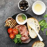 Appetizing snack with fried cheese haloumi, olives, bruschetta, tomatoes, olives, pine nuts, olive oil, honey and. Appetizing snack with fried cheese haloumi Stock Photos