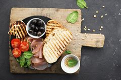 Appetizing snack with fried cheese haloumi, olives, bruschetta, tomatoes, olives, pine nuts, olive oil, honey and. Appetizing snack with fried cheese haloumi Royalty Free Stock Images