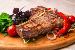 Appetizing steak on a bone, with tomatoes, pepper, on a wooden board. Horizontal frame stock image