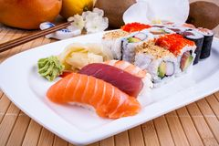 Appetizing sushi with wasabi, fruits and chopsticks Stock Images