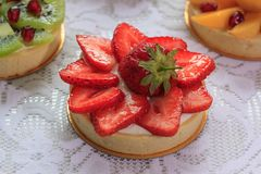 Appetizing tartlet with strawberry, apricot, kiwi, granatum. Sweeties dishes Stock Photos