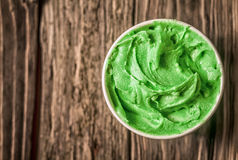 Appetizing tub of green Italian ice cream. For a delicious refreshing snack on a summer day served on an old wooden able with copyspace, view from above stock photos