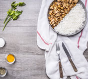 Appetizing turkey with onions and rice spread out on half the pan on a white napkin knife and fork with spices and herbs on g Stock Photography
