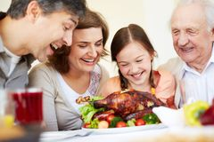 Appetizing turkey. Portrait of happy family looking at appetizing roasted turkey Stock Images