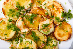 Appetizing vegetable marrows, fried in oil and strewed with gree Royalty Free Stock Photo