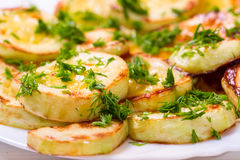 Appetizing vegetable marrows, fried in oil and strewed with gree Royalty Free Stock Images