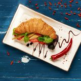 Appetizing veggie sandwich and olives in bowl. Appetizing veggie sandwich with croissant and vegetables lying on flat rectangular plate, bowl of olives and Royalty Free Stock Images