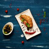 Appetizing veggie sandwich and olives in bowl. Appetizing veggie sandwich with croissant and vegetables lying on flat rectangular plate, bowl of olives and Stock Images