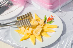 Appetizing view of fresh cheese pieces with mango on white ceramic plate Stock Photo