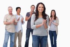 Applådera den unga kvinnan med vänner bak henne Arkivbild