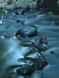Applådera på bergström, kör vatten över basaltstenblock, och bubblor skapar på jämnt mjölkaktigt vatten. Arkivbild