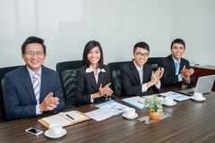 Applauding business team. Vietnamese business team applauding and looking at the camera Stock Images