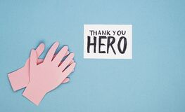 Applauding paper hands and the inscription thank you hero on a blue background