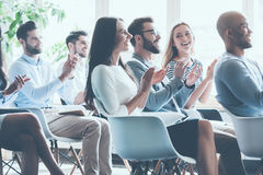 Applauding their achievements. Side view of group of young cheerful people sitting on conference together and applauding Royalty Free Stock Image