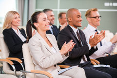 Applauding to speaker. Group of happy business people in formalwear sitting at the chairs in conference hall and applauding royalty free stock photo