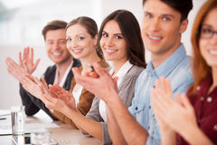 Applauding to you. Group of young people sitting together at the table and applauding to you stock images
