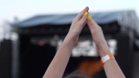 Applaus tegen achtergrond van scène en helder opvlammend licht, Partij van ventilators bij vrij rotsoverleg in openlucht, Handen  stock videobeelden