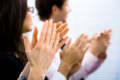 Applause. Businesspeople sitting in a row and applauding. Close-up on hands