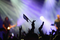 Applause in the concert and a rock band in background. Applause in a concert in front of a performing rock band royalty free stock image