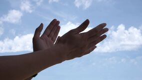 Applause. Woman hands applauding over blue sky background. Low angle view